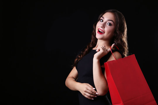 Happy woman with red shopping bag on black background