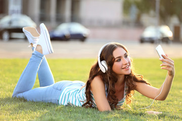 Young woman lying on green grass in the park and making selfie
