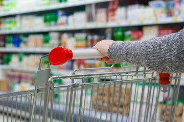 Women's hand on trolley in supermarket on the background of the racks with the consumer products in blur