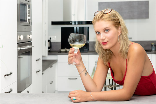 beautiful young blonde woman with red dress drinking white wine