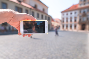 Tourist photographs the street of the old town on the camera of the smartphone. Phone is close-up and in focus.