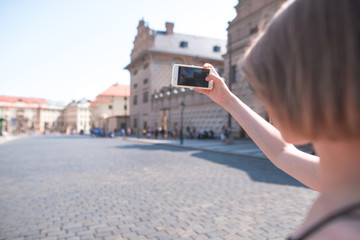 Tourist woman makes photographs of the old town on a smartphone. Walk the old streets on a sunny summer day. Mobile photography