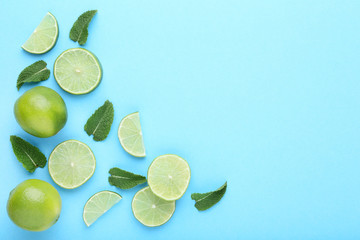 Ripe limes with green leafs on blue background