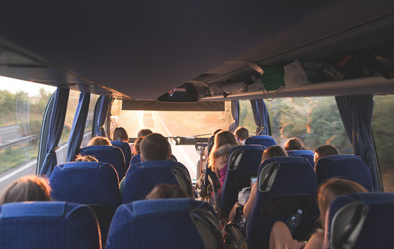 Tourist tour on the bus. People travel by bus. Salon of the great tourist bus with people at sunset