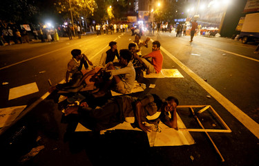 Supporters of the former Sri Lankan President Mahinda Rajapaksa, who leads the country's joint opposition, sleep on a main road during an anti-government protest in Colombo
