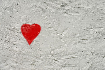 white rough wall with a small red painted heart