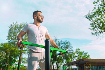 a young guy in good physical shape with a beard and in sunglasses trains on the simulators on the street in a city park on a hot sunny day in the summer