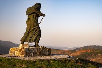 Statue eines Pilgers auf dem Jakobsweg mit Blick auf eine Gebirgskette nahe O Cebreiro bei Sonnenaufgang