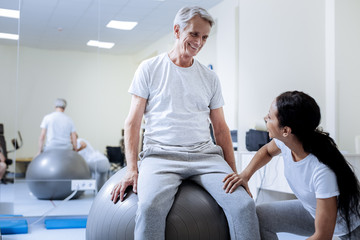 Funny ball. Positive enthusiastic aged man feeling excited while spending time in a professional rehabilitation center and sitting on a comfortable big fitball