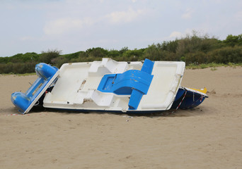 paddleboat destroyed on the beach