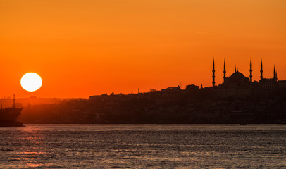 The sun sets over the Bosphorus. Istanbul, silhouette of the Blue Mosque.