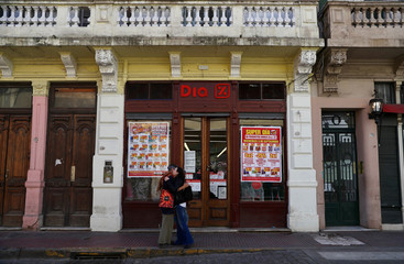 Two women embrace outside a supermarket in Buenos Aire