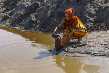 girl of oriental appearance in sari and hijab fills the pitcher with water from a dirty source in the desert