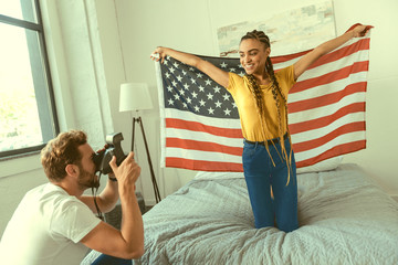 Give me a smile. Mindful young gentleman taking a photo of his beautiful girlfriend posing with an American flag on a bed.