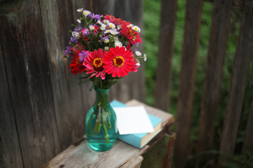 a summer bouquet with zinnias in a glass bottle ,and a book on the old wooden  bench/birthday /mother day/love card