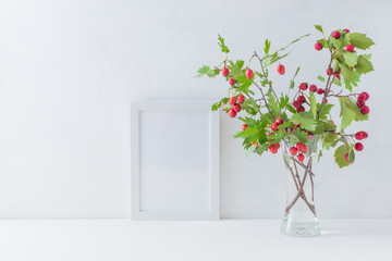 Mockup white frame and branches with red berries
