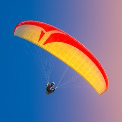 Foto auf Acrylglas Luftsport Beautiful yellow and red paraglider flying in colorful sky