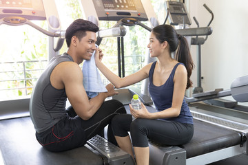 Muscular couple discussing and lexax front of treadmill machine and holding water bottle in fitness gym