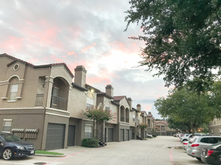 Typical apartment complex condos with attached garage and uncovered parking lots at suburban area in Irving, Texas, USA.