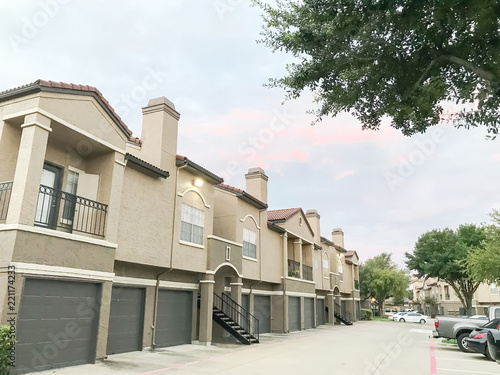 Typical Apartment Complex Condos With Attached Garage And Uncovered Parking Lots At Suburban Area In Irving