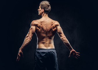 Back view of shirtless man with stylish hair and muscular ectomorph posing on the dark textured background.