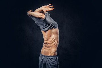Stylish ectomorph bodybuilder with stylish hair takes off his shirt on the dark background.