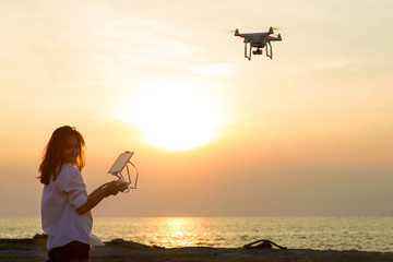 Silhouette of young woman using drone at sunset for photos and video making - Happy woman having fun with new technology trends in sky and sea.