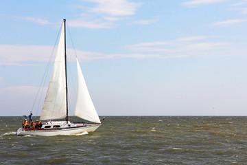 Sailboat yacht rushes along the waves.
