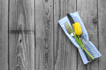 Grey wooden background with yellow tulip decoration