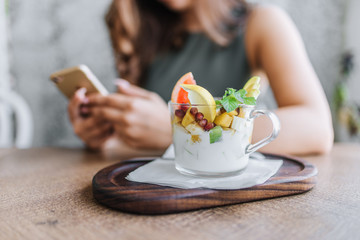 Young businesswoman having her healthy snack while working on her phone.