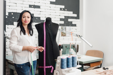 Professional female dressmaker working and using measuring tape