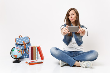 Young funny woman student doing taking selfie shot on mobile phone and blowing lips sitting near globe backpack, school books isolated on white background. Education in high school university college.