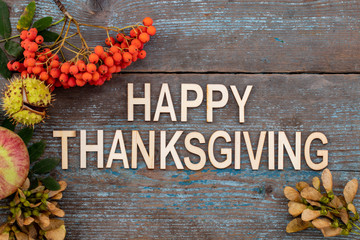 Happy Thanksgiving Day - text  with Autumn background from fallen leaves and fruits with vintage place setting on old wooden table