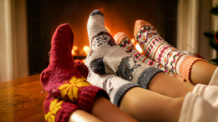 Closeup image of mothers, fathers, and childs feet in woolen socks lying next burning fireplace