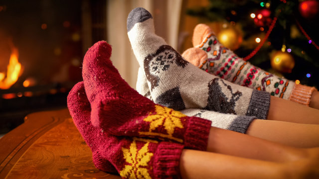 Closeup image of family in warm knitted socks lying next to fireplace and Christmas tree