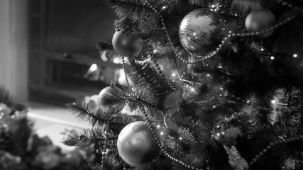 Black and white image of decorated Christmas tree in living room