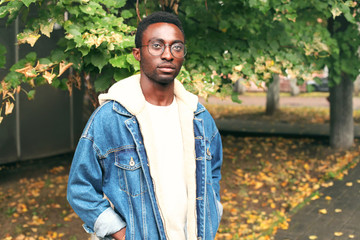 Wall Mural - Fashion african man wearing jeans jacket, eyeglasses in autumn park
