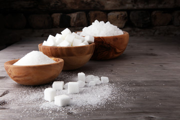 Bowl with white sand, crystal and lump sugar on wooden background. Wall mural
