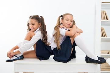 School break concept. Schoolgirls cute pony tails hairstyle sit on desk. Best friends free relaxing...