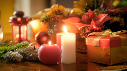 Closeup image of burning candles on wooden table against Christmas wreath