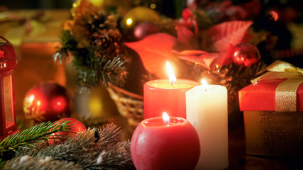 Closeup image of three burning candles and beautiful Christmas wreath on wooden table