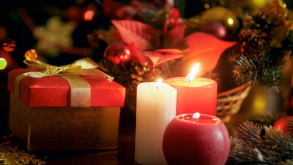 Closeup photo of three candles burning next Christmas gifts and decorative wreath
