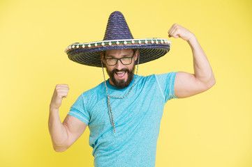 Man cheerful face in sombrero hat posing with biceps muscles strong gesture yellow background. Mexican party concept. Guy looks festive in sombrero. Party and holiday. Mexican traditional attribute