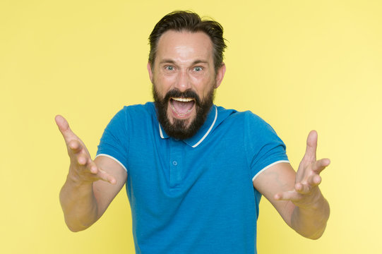 What are you doing. Stop annoying him. Overwhelmed with emotions. Handsome shouting mature man screaming standing against yellow background. Man bearded irritated annoyed can not keep calm anymore