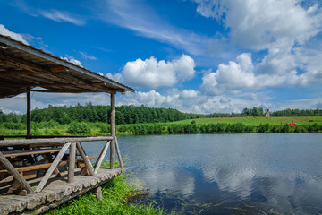 arbor for rest of wooden logs on the shore of a picturesque lake or river with green coasts against the background of beautiful nature and a blue sky with clouds