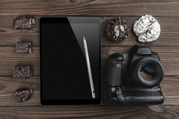 Top view of a camera photo, tablet in high definition with silver pen and sweets on a wood dark background