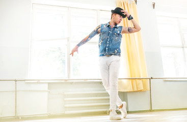 Modern tattooed art dancer teenager dressed in jeans vest, white pants and black hat dancing and mirror posing portrait