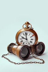 vintage broken pocket watch old binoculars on a light background with toning