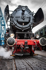 Steamy and rolling old locomotive with red steel wheels on on-site shunting platform, authentic industrial details and craftsmanship along the rail way and train station