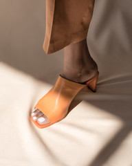 Stepping into the light, high fashion female model foot